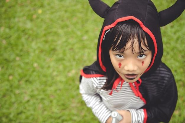 Fröhliches halloween! das süße kleine mädchen im halloween-kostüm