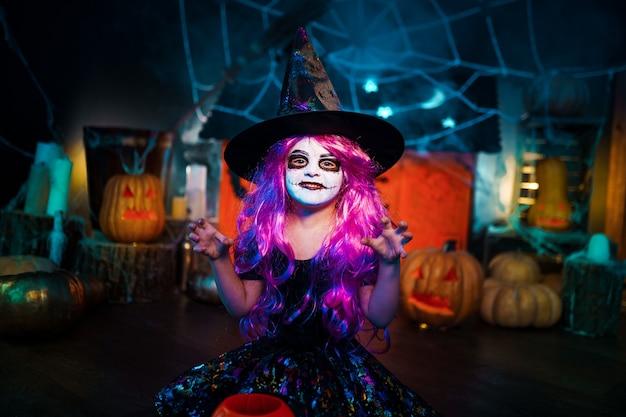 Fröhliches halloween. ein kleines schönes mädchen in einem hexenkostüm feiert zu hause in einem innenraum mit kürbissen und pappmagiehaus auf dem hintergrund