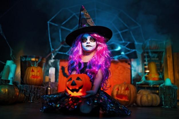 Fröhliches halloween. ein kleines schönes mädchen in einem hexenkostüm feiert zu hause in einem innenraum mit kürbissen und pappmagiehaus
