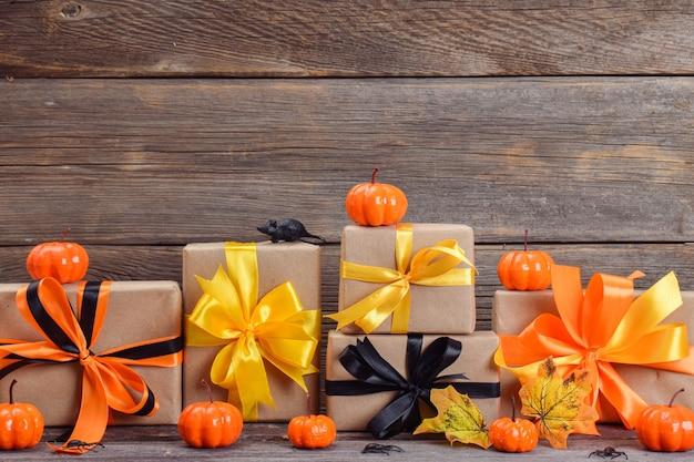 Fröhliches halloween. festliche komposition für halloween auf einem hölzernen hintergrund mit kürbissen und geschenken. platz kopieren.