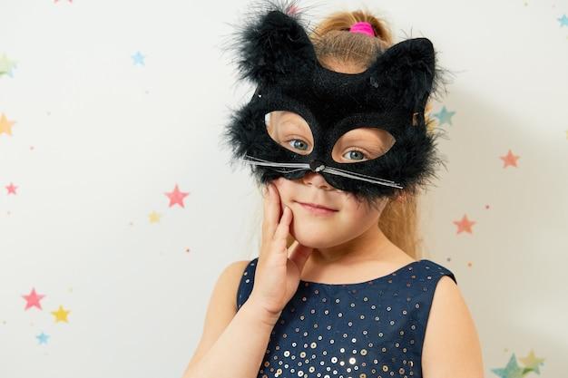 Fröhliches halloween . kleines mädchen in schwarzer katzenmaske, karnevalskostüm. lustiges gesicht