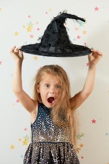Fröhliches halloween. kleines mädchenkind im hexenkarnevalskostüm und im schwarzen hut. lustiges gesicht