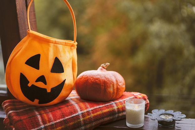 Fröhliches halloween. kürbis und kerzen auf einem gemütlichen fensterbrett mit rotem plaid. der herbst ist gemütlich