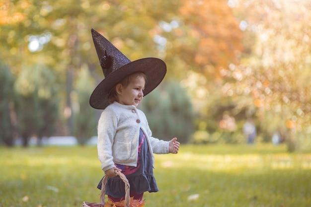 Fröhliches halloween. porträt des netten kleinkindmädchens im hexenhut im herbstwald.