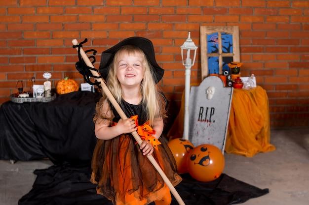 Fröhliches halloween. porträt eines netten blonden mädchens im kostüm im stil halloweens. kleines kind feiert halloween. mädchen im orange schwarzen hexenhalloween-kostüm mit besen. party-konzept