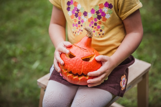 Fröhliches halloween. schönes lächelndes mädchen setzt auf holzstuhl und hält kleinen kürbis jack o lanterns draußen
