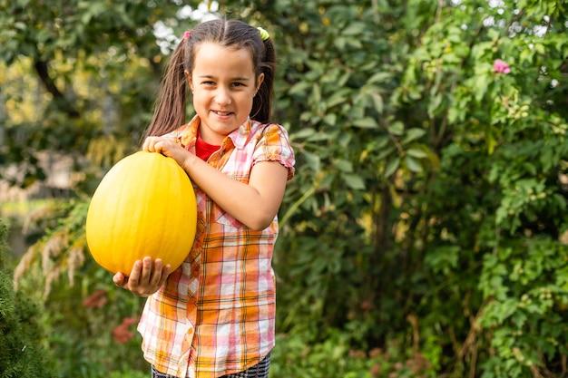 Fröhliches halloween, süßes kleines mit einem kürbis in den händen.