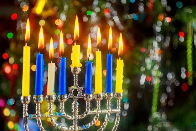 Fröhliches hanukkah. zurückhaltendes bild des jüdischen feiertags mit menorah der fokus der nachtansicht heraus
