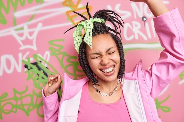 Fröhliches hipster-mädchen mit gekämmten dreadlocks hat goldene zähne tanzt sorglos gegen bunte graffiti-wand trägt modische kleidung und lächelt breit