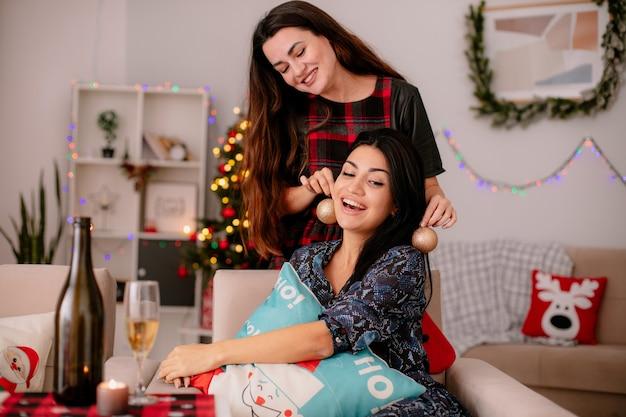 Fröhliches hübsches junges mädchen hält glaskugelverzierungen in der nähe der ohren ihrer freunde, die auf einem sessel sitzen und die weihnachtszeit zu hause genießen