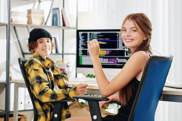 Fröhliches hübsches junges mädchen und ihr bruder lächeln in die kamera, wenn sie am schreibtisch sitzen und hausaufgaben für den informatikunterricht machen