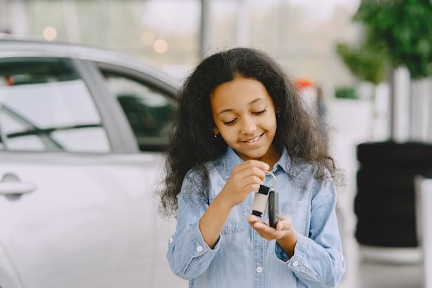 Fröhliches, hübsches kleines mädchen, das autoschlüssel hält, es zeigt, lächelt und posiert.