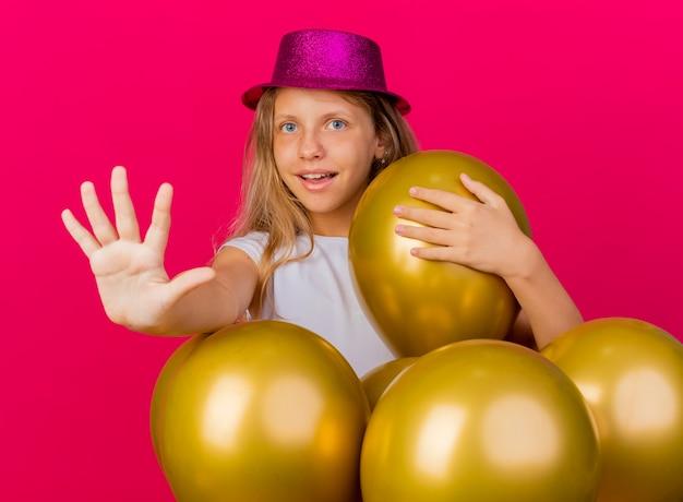 Fröhliches hübsches kleines mädchen im feiertagshut mit bündel von ballons, die kamera betrachten, die sto zeichen mit hand lächelnd, geburtstagsfeierkonzept, das über rosa hintergrund steht