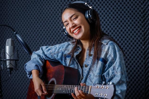 Fröhliches, hübsches lächeln des porträts einer jungen asiatischen sängerin, die kopfhörer mit einer gitarre trägt, die in einem professionellen studio ein lied vor dem mikrofon aufnimmt