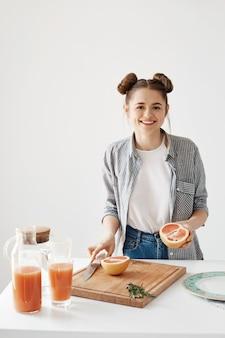 Fröhliches hübsches mädchen lächelnd, das grapefruit zum frühstück über weißer wand schneidet. gesunder detox-smoothie. fitness essen.