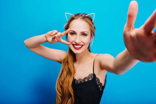 Fröhliches hübsches mädchen mit katzenohren in den diamanten auf kopf posiert, nimmt selfie, zeigt frieden, genießt party. trägt ein schwarzes kleid, hat schöne blaue augen und langes, welliges haar.