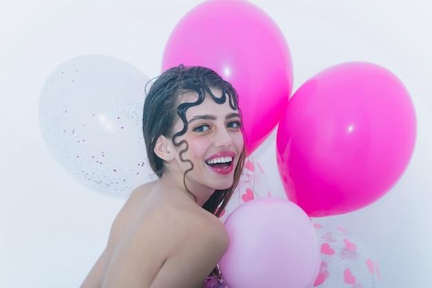 Fröhliches hübsches mädchen oder sexy frau mit süßem, lockigem lock, blonden haaren, modischer frisur und rosigen lippen, stilvollem make-up, auf jungem gesicht lächelnd mit partyballons, rosa, herzen auf weißem hintergrund