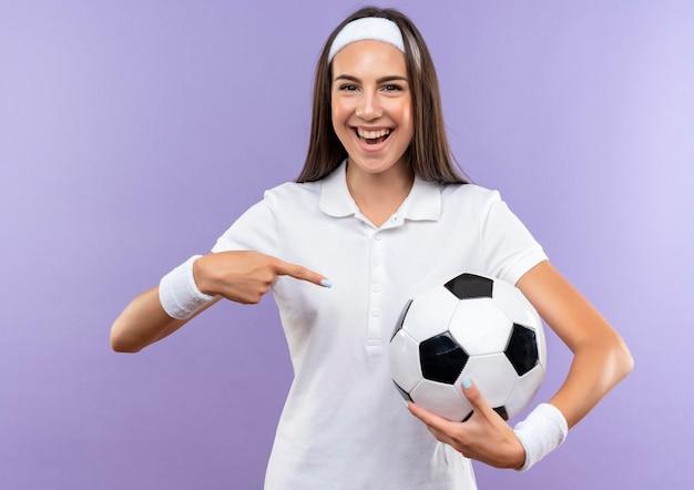 Fröhliches hübsches sportliches mädchen, das stirnband und armband trägt und auf fußball zeigt, isoliert auf lila wand