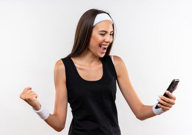 Fröhliches hübsches sportliches mädchen mit stirnband und armband, das das handy hält und betrachtet, das die faust isoliert auf weißer wand hebt