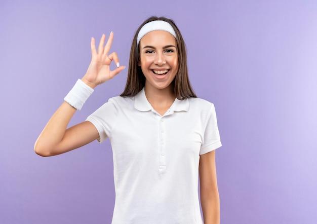 Fröhliches, hübsches, sportliches mädchen mit stirnband und armband, das ein okay-schild macht, isoliert auf lila wand mit kopierraum