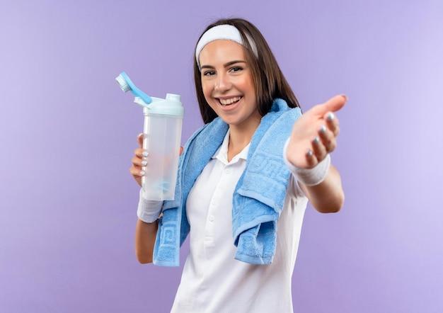 Fröhliches hübsches sportliches mädchen mit stirnband und armband, das eine wasserflasche hält und die hand mit einem handtuch am hals ausstreckt, isoliert auf lila wand purple