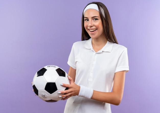 Fröhliches hübsches sportliches mädchen mit stirnband und armband, das fußball isoliert auf lila wand hält