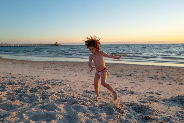 Fröhliches jungenkind, das in den sommerferien am strand spielt kinder in der natur mit schönem meeressand und...