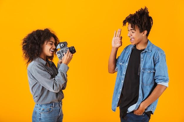 Fröhliches junges afrikanisches paar, das isoliert steht und ein video mit kamera macht