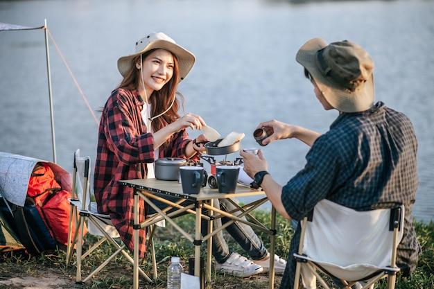 Fröhliches junges backpacker-paar mit trekkinghut, das in der nähe des sees mit kaffee und frühstück sitzt und während des campingausflugs im sommerurlaub frische kaffeemühle macht
