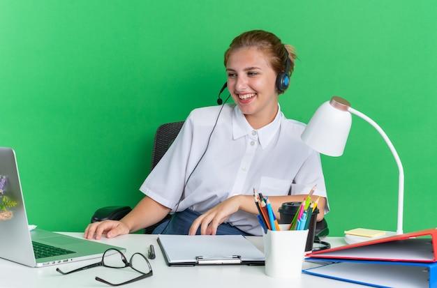 Fröhliches junges blondes callcenter-mädchen mit headset am schreibtisch sitzend mit arbeitswerkzeugen, die die hand auf dem schreibtisch halten und auf den laptop schauen