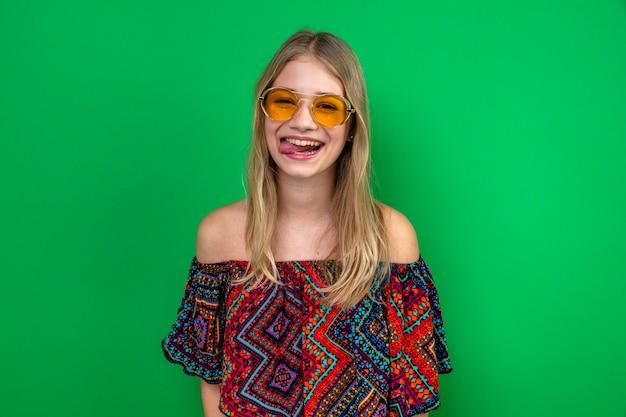 Fröhliches junges blondes slawisches mädchen mit sonnenbrille, die ihre zunge herausstreckt und