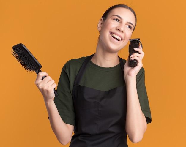 Fröhliches junges brünettes friseurmädchen in uniform mit haarschneidemaschinen und kamm, das auf die seite schaut