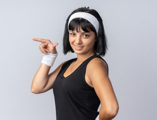 Fröhliches junges fitness-mädchen mit stirnband, das die kamera ansieht und selbstbewusst lächelt und mit dem zeigefinger auf die seite zeigt, die über weiß steht