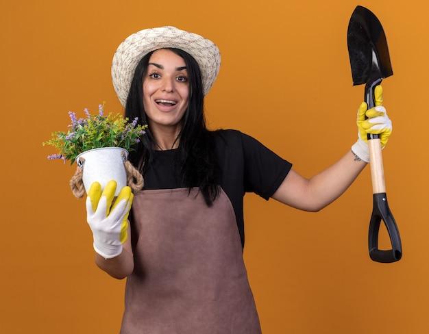 Fröhliches junges gärtnermädchen, das uniform und hut mit gärtnerhandschuhen trägt, die spaten und blumentopf halten und vorne isoliert auf oranger wand schauen