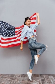 Fröhliches junges glückliches mädchen, das usa-flagge hält und über graue wand springt