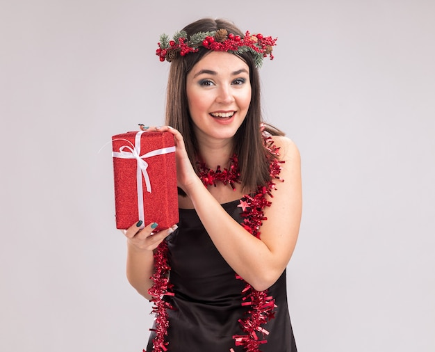 Fröhliches junges hübsches kaukasisches mädchen, das weihnachtskopfkranz und lametta-girlande um den hals trägt, das geschenkpaket hält und die kamera einzeln auf weißem hintergrund mit kopienraum betrachtet