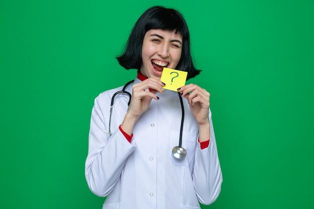 Fröhliches junges hübsches kaukasisches mädchen in arztuniform mit stethoskop, das gelbe karte mit fragezeichen hält