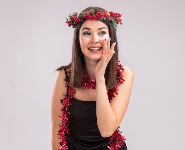 Fröhliches junges hübsches kaukasisches mädchen mit weihnachtskopfkranz und lametta-girlande um den hals, das auf die seite flüsternd auf weißem hintergrund mit kopienraum schaut