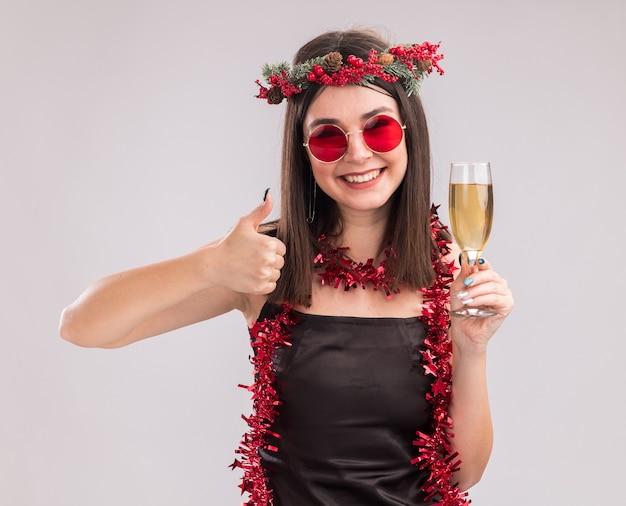 Fröhliches junges hübsches kaukasisches mädchen mit weihnachtskopfkranz und lametta-girlande um den hals mit brille, die ein glas champagner hält und in die kamera schaut, die den daumen einzeln auf weißem hintergrund zeigt