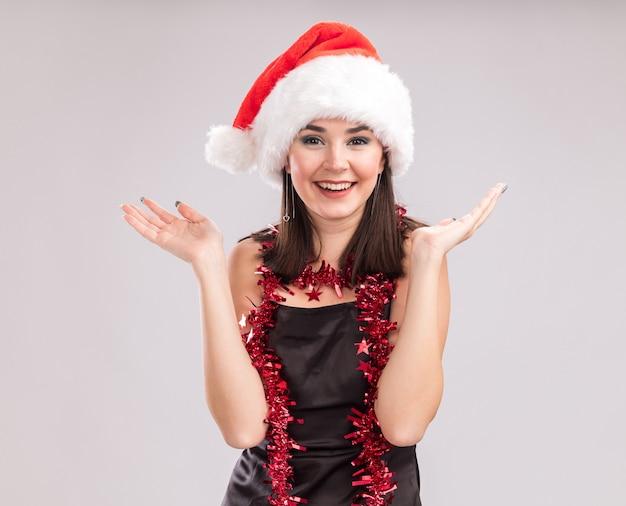 Fröhliches junges hübsches kaukasisches mädchen mit weihnachtsmütze und lametta-girlande um den hals, das in die kamera schaut, die leere hände isoliert auf weißem hintergrund zeigt