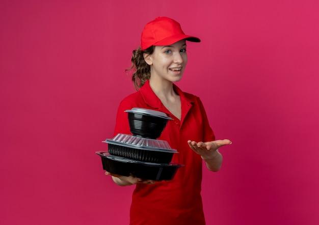 Fröhliches junges hübsches liefermädchen mit roter uniform und mütze, das mit der hand auf lebensmittelbehälter zeigt und zeigt