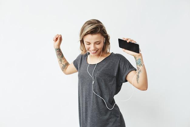 Fröhliches junges hübsches mädchen lächelnd, das musik im kopfhörertanzen hört.