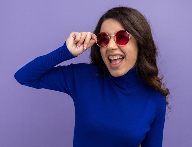 Fröhliches junges hübsches mädchen mit sonnenbrille, das eine brille mit blick auf die seite greift