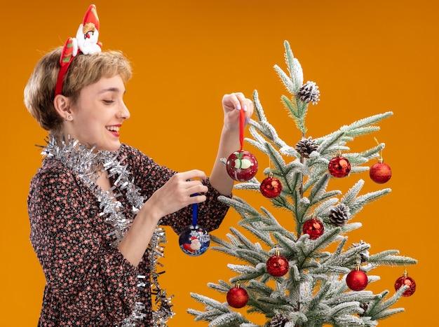 Fröhliches junges hübsches mädchen mit weihnachtsmann-stirnband und lametta-girlande um den hals, das in der nähe des weihnachtsbaums in der profilansicht steht und ihn mit weihnachtskugeln lacht, isoliert auf oranger wand