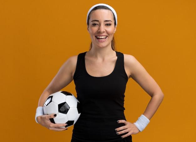 Fröhliches junges hübsches sportliches mädchen mit stirnband und armbändern, das die hand an der taille hält und den fußball isoliert auf der orangefarbenen wand hält