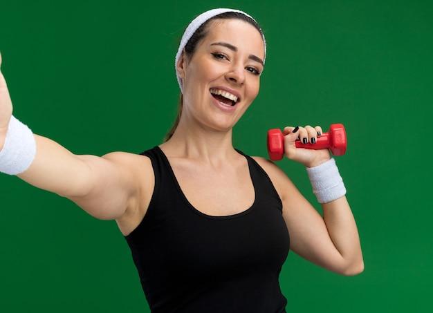 Fröhliches junges hübsches sportliches mädchen mit stirnband und armbändern, das eine hantel hält und die hand in richtung kamera ausstreckt, isoliert auf grüner wand