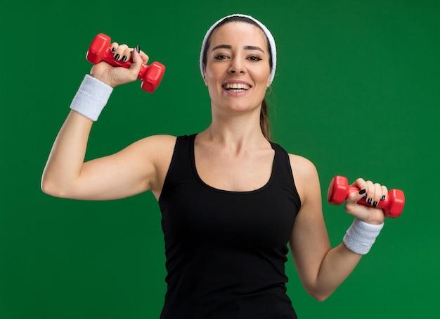 Fröhliches junges hübsches sportliches mädchen mit stirnband und armbändern mit hanteln