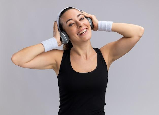 Fröhliches junges hübsches sportliches mädchen mit stirnband und armbändern mit kopfhörern, das die hände auf die kopfhörer legt und musik hört, isoliert auf weißer wand