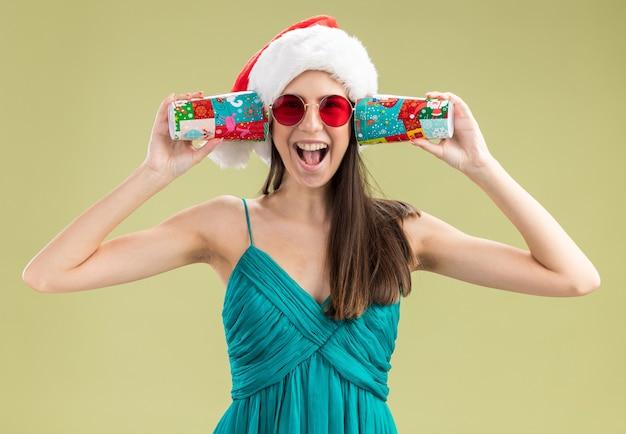 Fröhliches junges kaukasisches mädchen in sonnenbrille mit weihnachtsmütze, das pappbecher auf den ohren hält, isoliert auf olivgrüner wand mit kopierraum