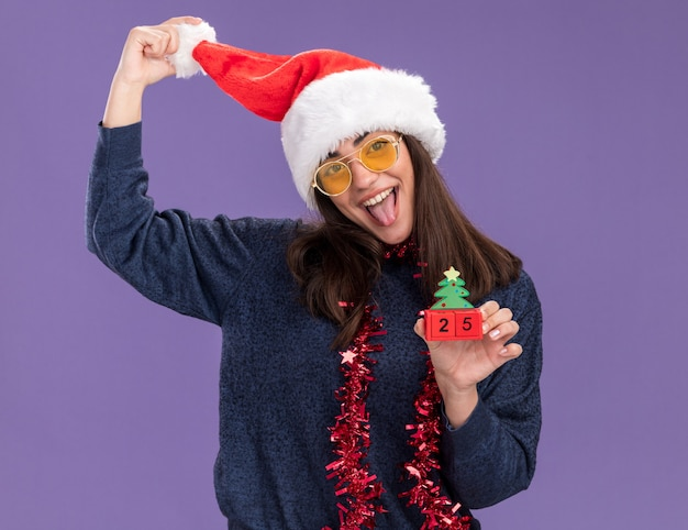 Fröhliches junges kaukasisches mädchen in sonnenbrille mit weihnachtsmütze und girlande um den hals streckt die zunge heraus und hält weihnachtsbaumschmuck isoliert auf lila wand mit kopierraum